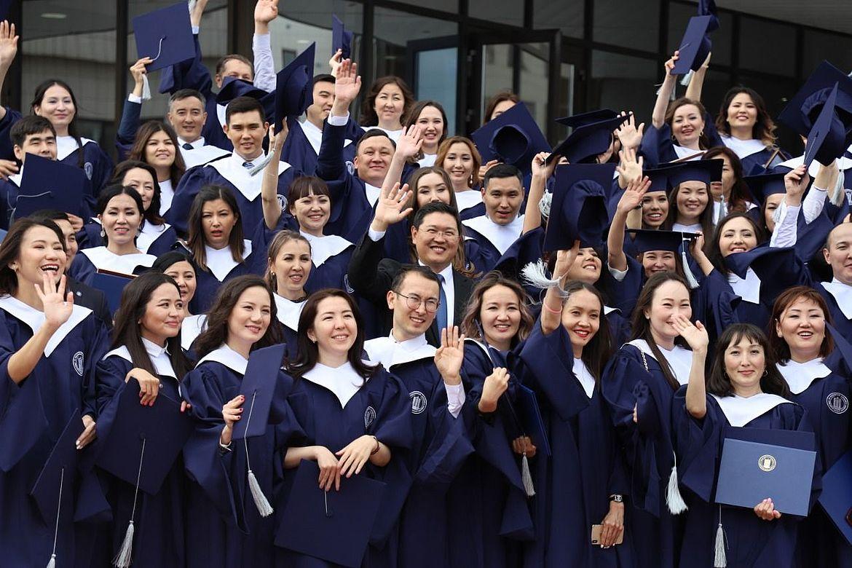 Eine große Gruppe Absolventen jubelt.